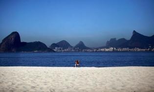 A man sunbathes at the Praia de Icarai beach in Niteroi